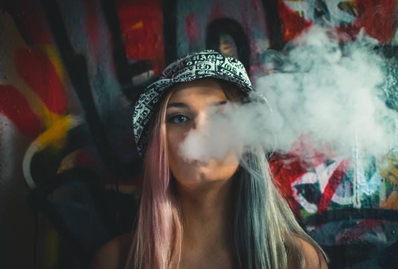 une fille fume une cigarette électronique