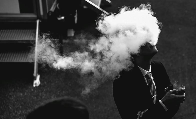 un homme fume une cigarette électronique