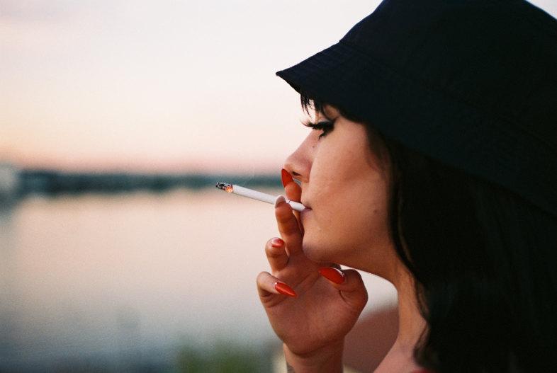 une fille fume une cigarette