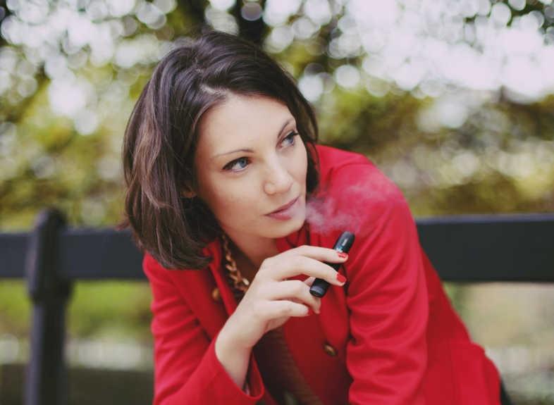 Une fille fume une cigarette électronique sans prendre de poids
