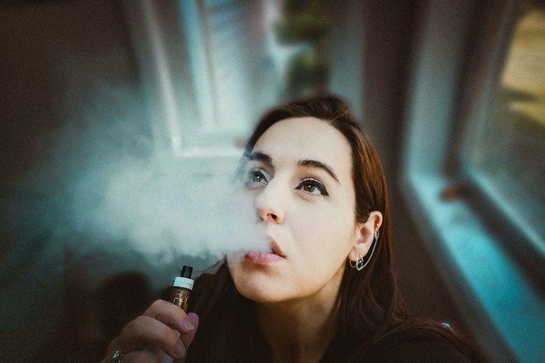 Fille à l'aide de cigarette électronique pour coup de joue