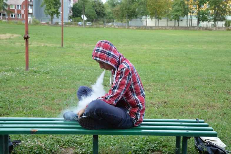 Homme vaporisant des liquides e-cigarette