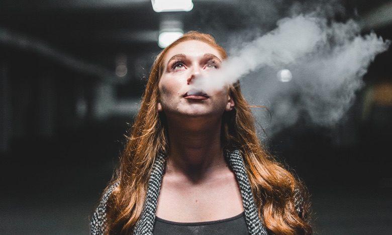 Femme vapotante avec une cigarette électronique