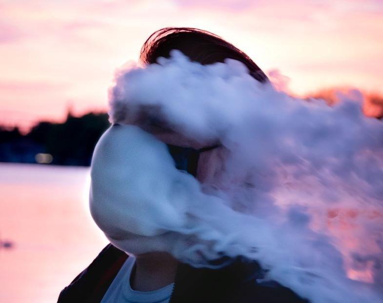 Guy vapotant après avoir remplacé les bagues de sa e-cigarette